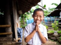 Suchat, a boy in Thailand, smiles and holds his hands in prayer. He is wearing a white collared shirt. A rural home and plants are seen behind him