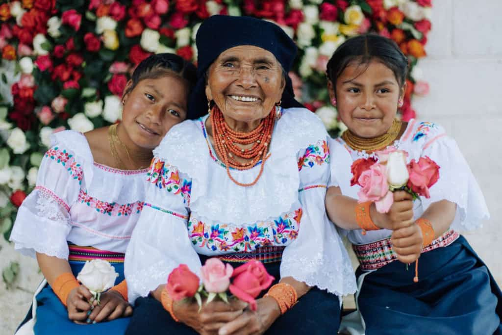 Angelita is sitting in the middle of her two granddaughters. They are all wearing traditional clothing and are holding roses. Behind them is a wall of roses.