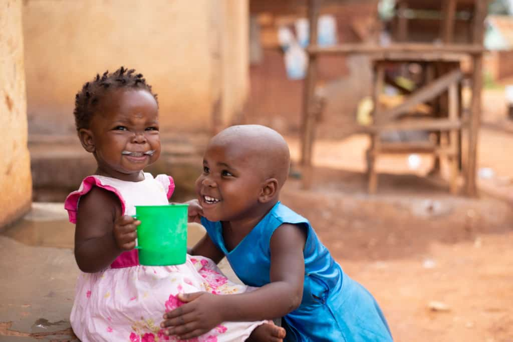 A toddler smiles with porridge on her face. She is wearing a pink dress and holding a green cup of porridge. Her sister is smiling next to her, wearing a blue dress.