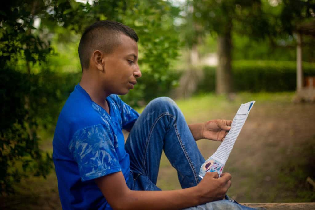 Carlos is wearing jeans and a blue shirt. He is sitting down outside reading one of his sponsor's letters. There are trees in the background.