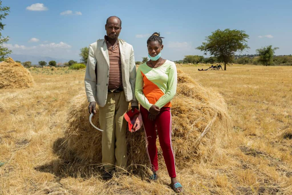 Dagem is wearing red pants, an orange and green shirt, and a face mask. She is standing next to her father in a field where they are harvesting crops.