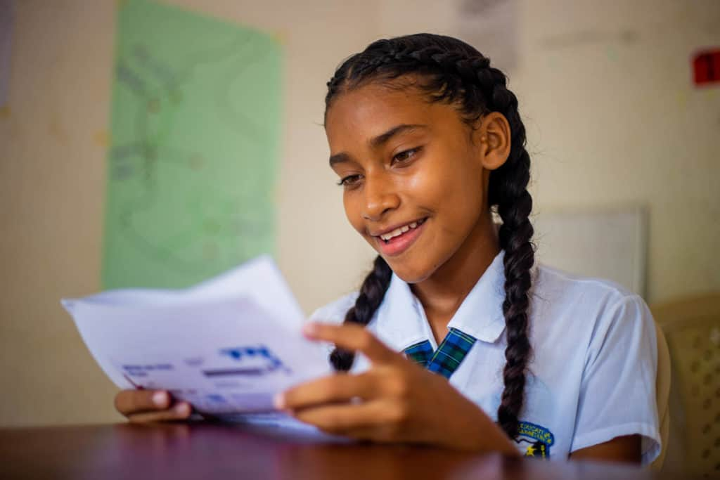 Sara, in a white uniform shirt, is sitting at a table at the project. She smiles while reading a letter she received from her sponsor Pamela.