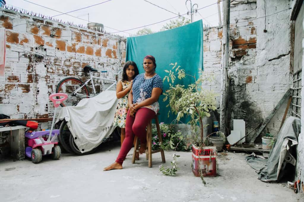 Danielly is wearing a blue shirt and maroon pants. She is sitting on a stool outside her home in front of a green background. Her daughter, Rayane, is standing next to her.