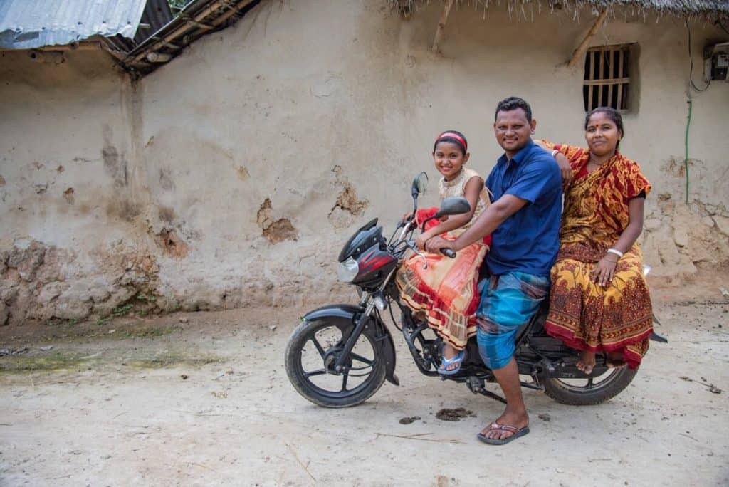 A young girl sits on the front of a motorcycle. Behind her is her father and her mother. They are wearing colorful clothing.