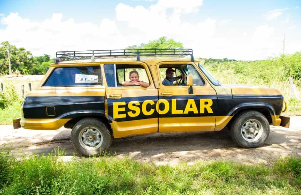 """A black and yellow jeep truck vehicle reading """"Escolar"""" is parked on a dirt road. A smiling girl looks out the window."""