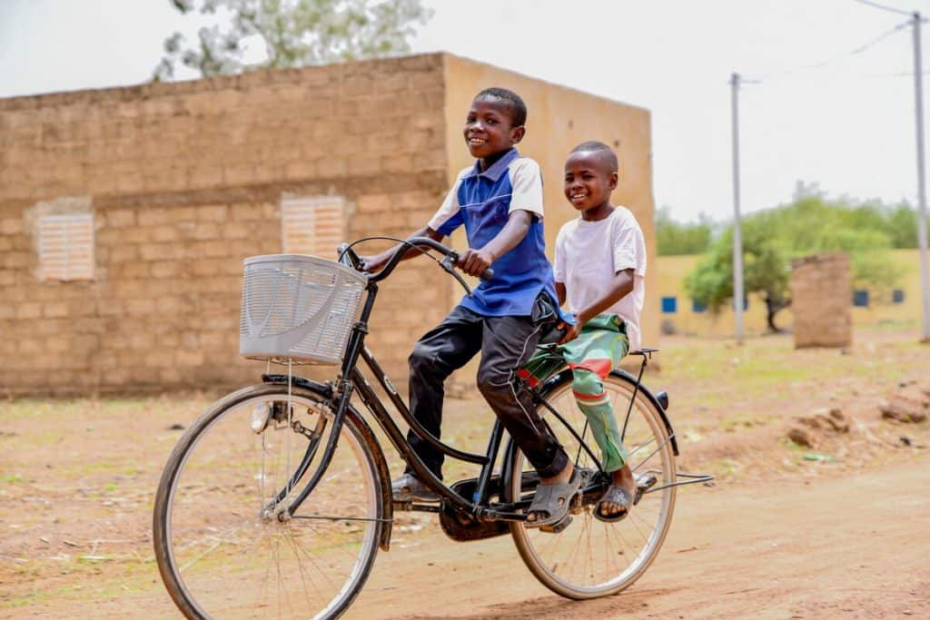 Two boys ride on a bicycle down a dirt road in Burkina Faso.
