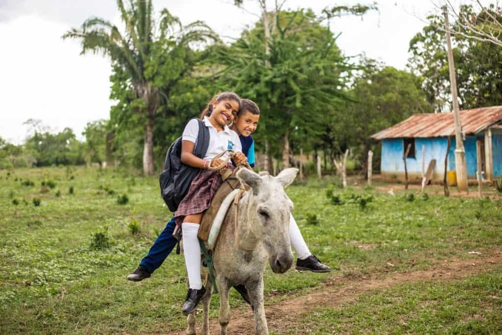 A brother and sister ride on a donkey. The girl is wearing a school uniform and backpack.