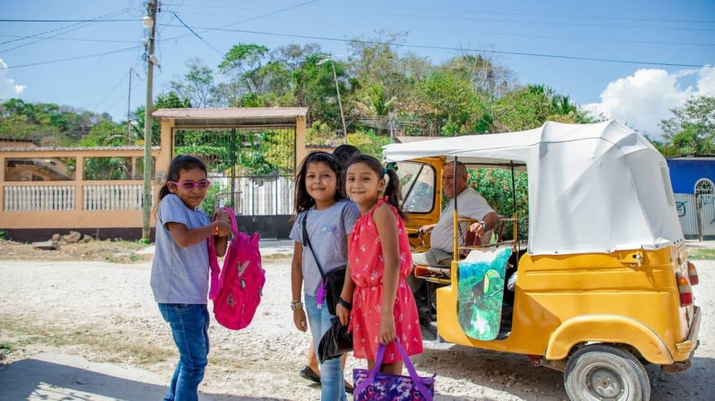 Three girls, friends, are getting ready to board a yellow tuk-tuk vehicle, which a man is driving.