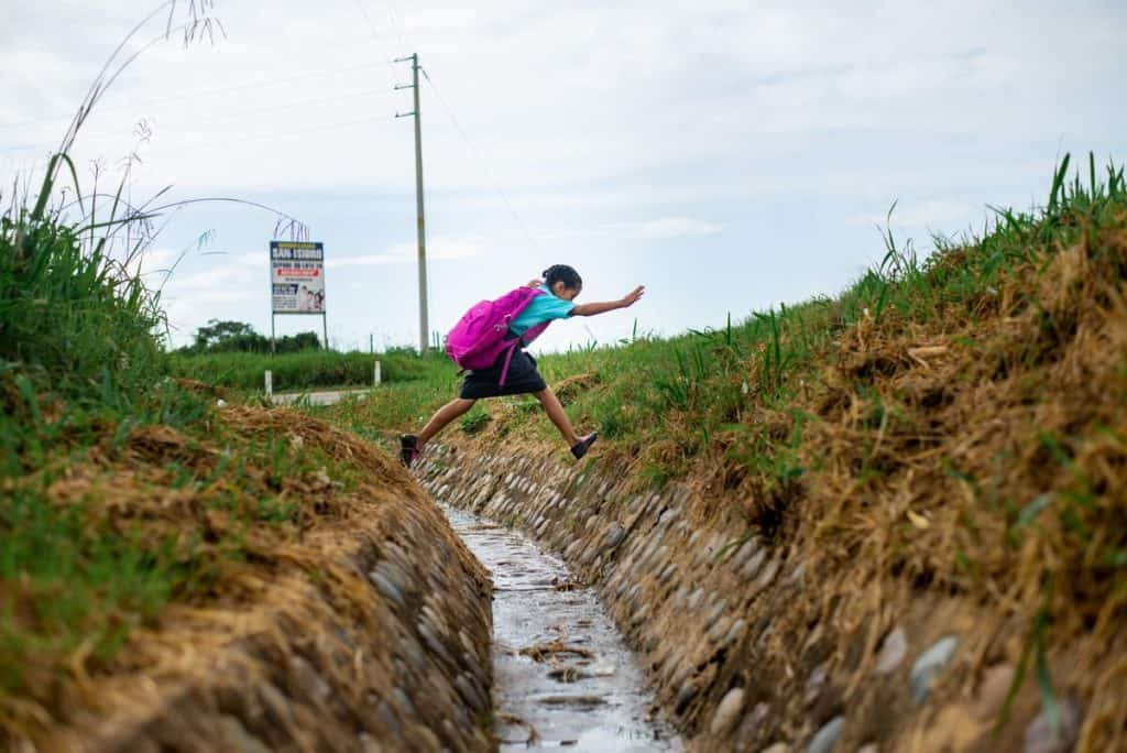 A girl wearing a blue shirt and pink backpack jumps across a ditch. There is water running down the ditch.