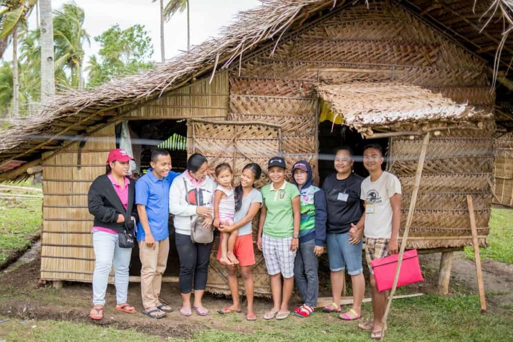 A group of people stands in front of a tiny home made of woven straw in the Philippines. A young woman holds a small girl in her arms, and church workers smile near them.
