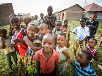 A group of children and youth smile outside in Rwanda
