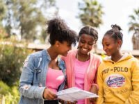 Three teenage girls smile as one of them holds a letter from her Compassion sponsor.