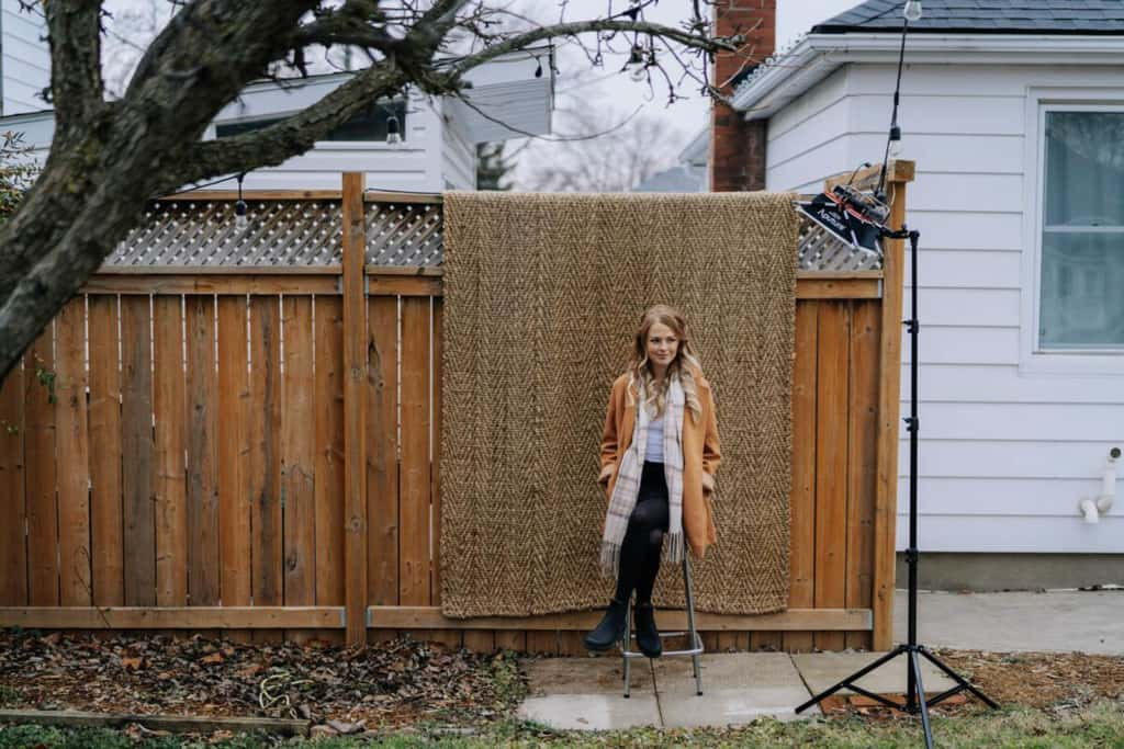 Becky is sitting on a stool in her back yard. Behind her is a wooden privacy fence with a brown rug hanging over it.