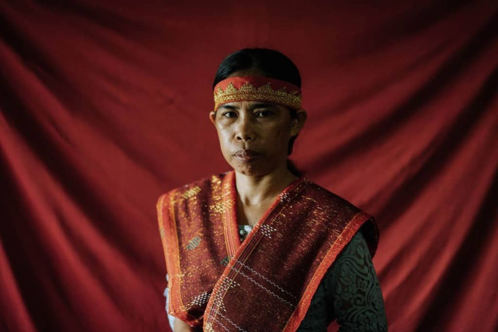 Marhati is sitting in her home in front of a red backdrop. She is wearing traditionally woven clothing.