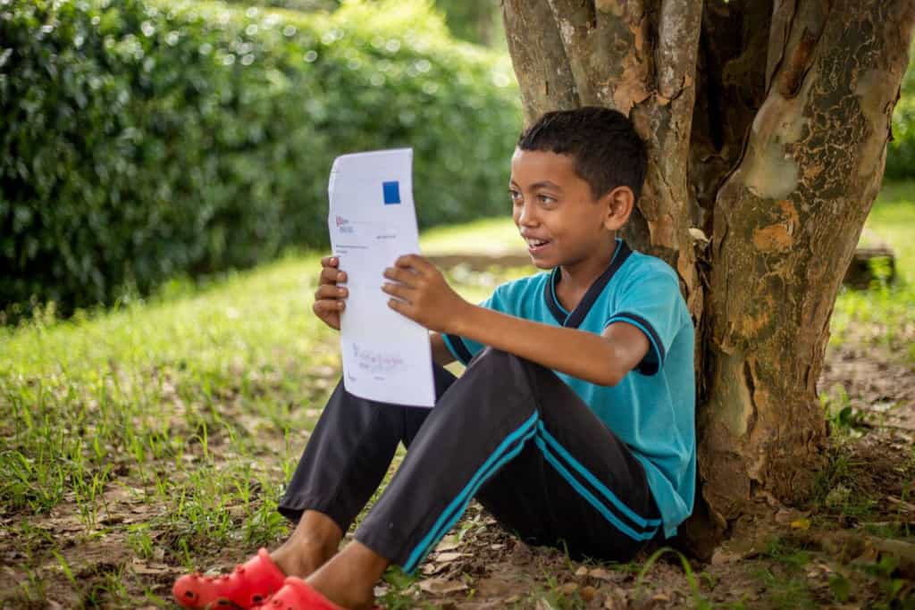Carlos is wearing a blue shirt and black pants. He is outside, sitting against a tree, and reading a letter from his sponsor.