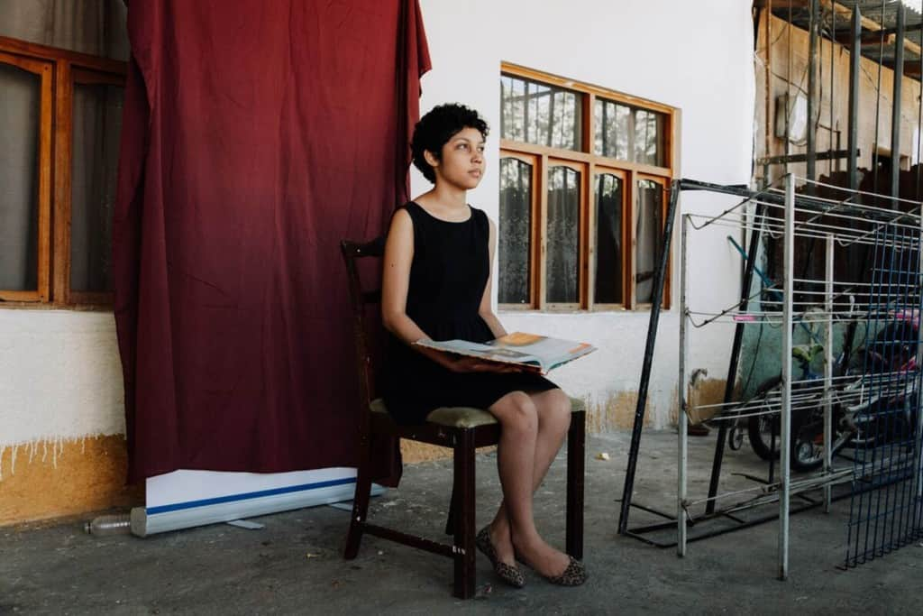 Diana is wearing a black dress. She is sitting in a chair in front of a red backdrop in her home and is holding a book.