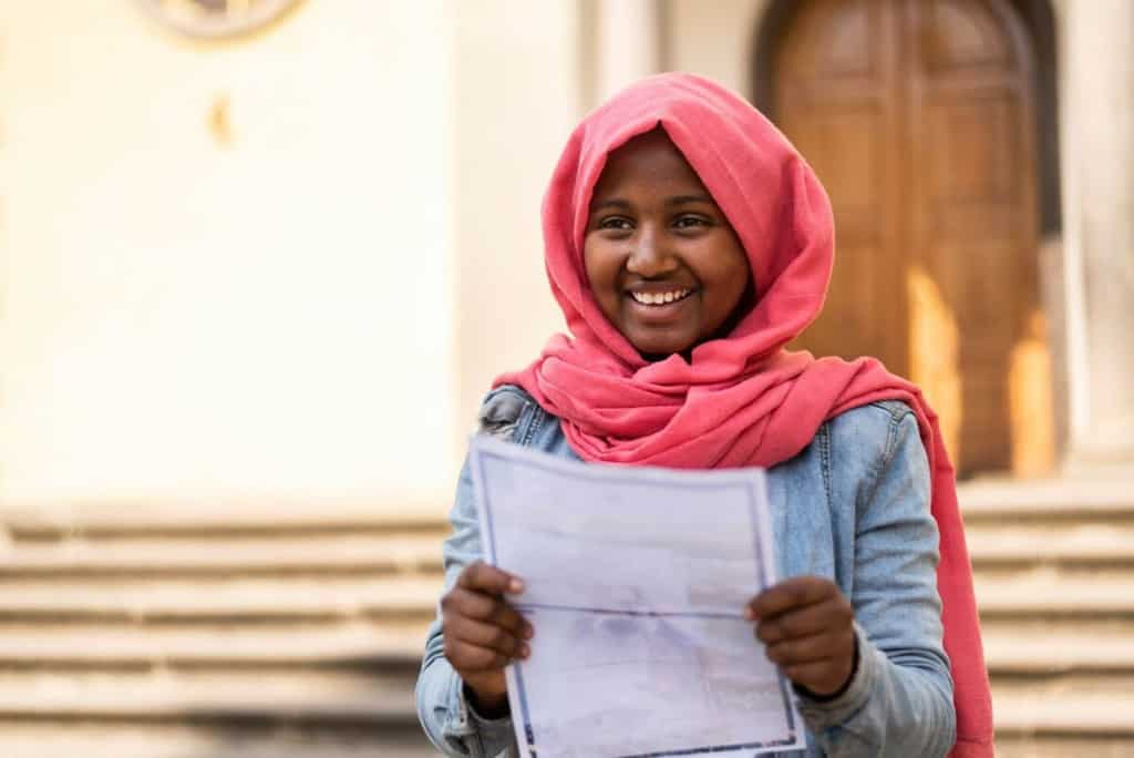 Liya is wearing a jean jacket and a pink head covering. She is standing outside and is holding a letter from her sponsor.