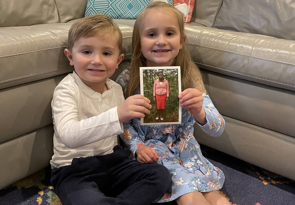 Two young children are smiling and holding a photo of the youth their family sponsors through Compassion.