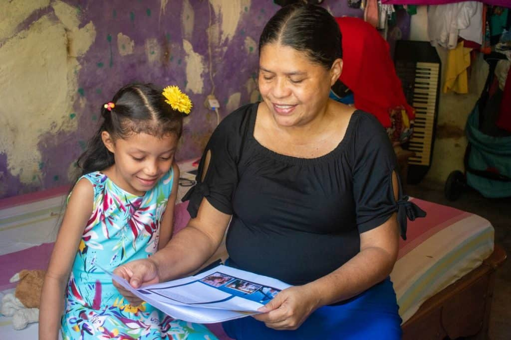 Abigail is wearing a blue dress with a bright floral pattern. She is sitting on her bed with her mother, Claudia. They are reading one of Abigail's sponsor letters.