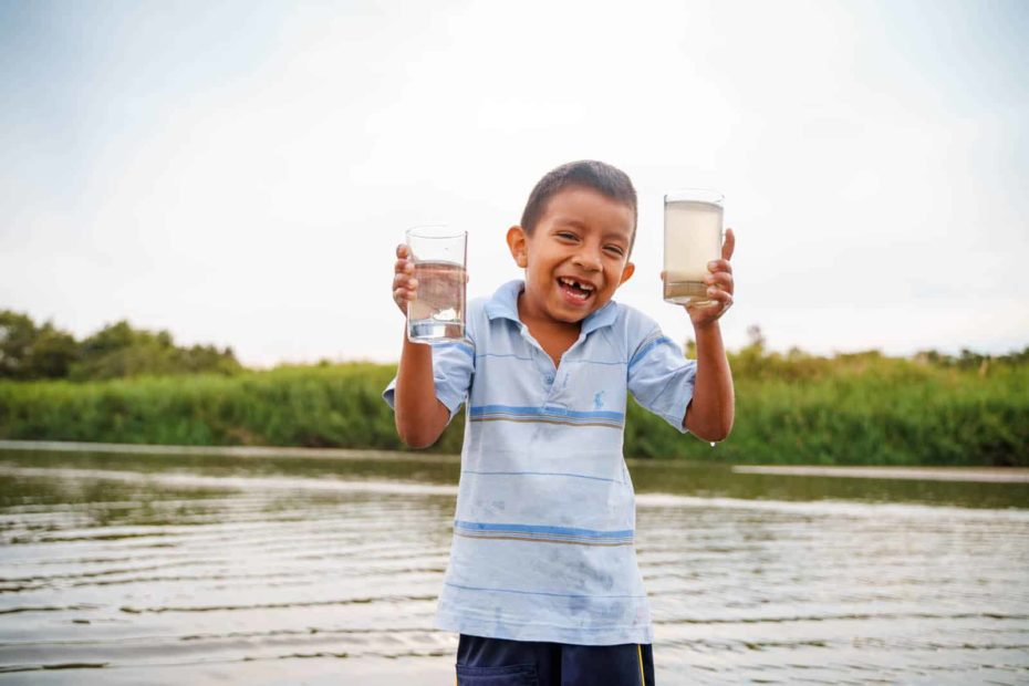 A boy wearing a light blue shirt is standing in front of a body of water. He is holding a glass of water in each hand. One glass contains clean water and one contains dirty water. There are trees behind the water.