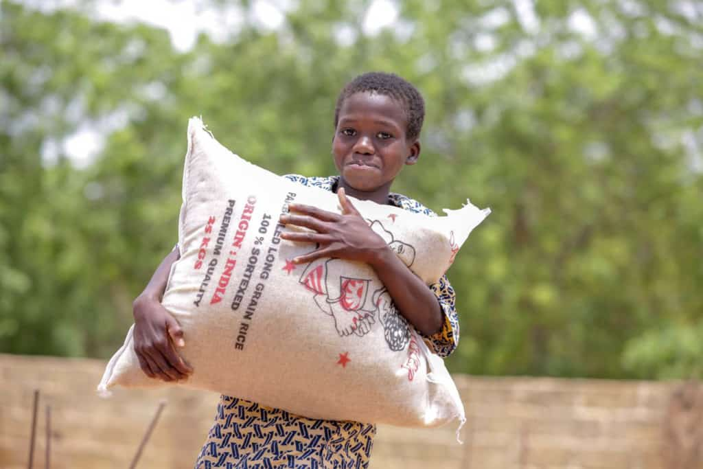 A child is seen here smiling at the camera and carrying a large bag of food. There is a brick wall and trees in the background.