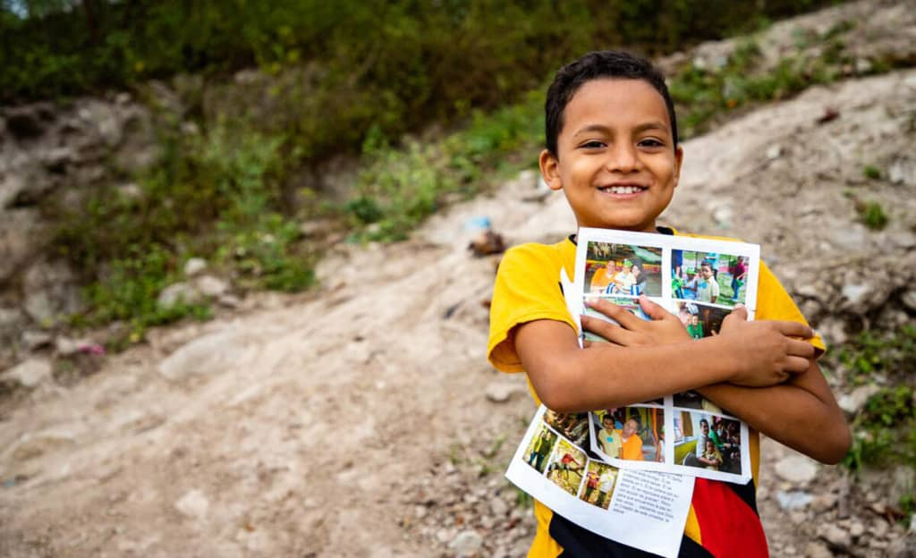 Boy wearing a yellow shirt and jeans. He is standing outside his home and is holding his sponsor letters close to his chest.