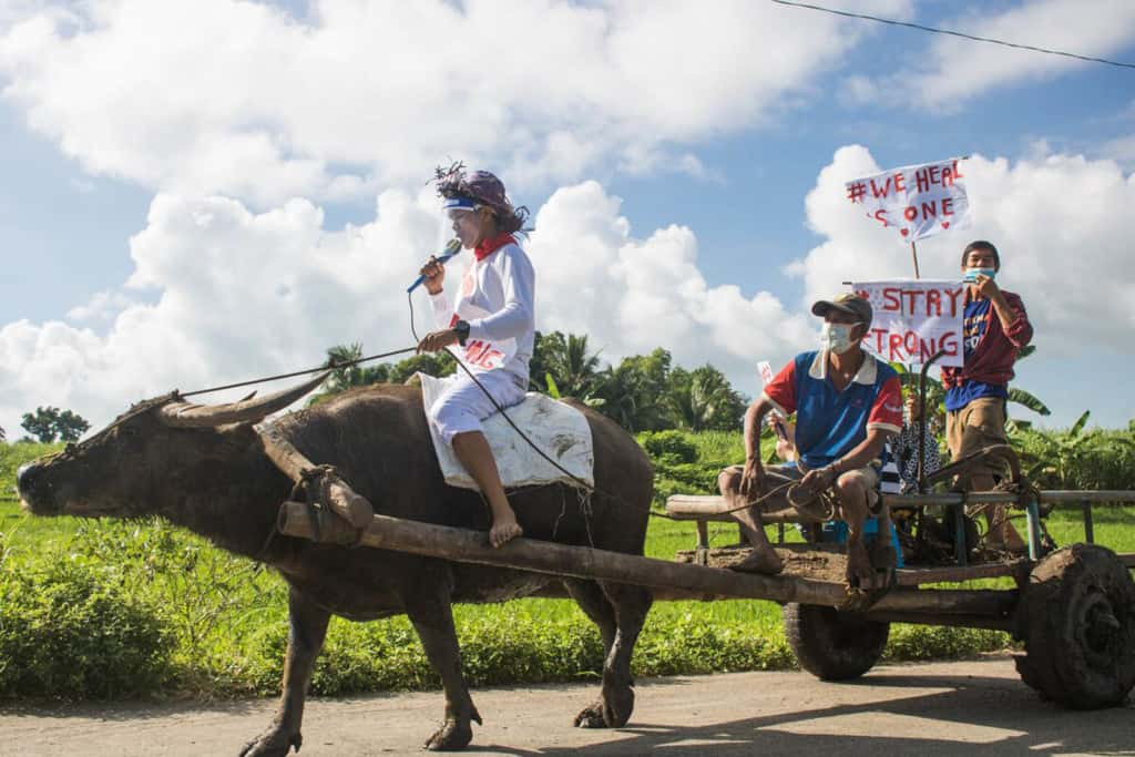 A boy and his carabao (water buffalo) karaoke challenge. They are walking down a road and people are holding signs as they sit in a cart pulled by the water buffalo.