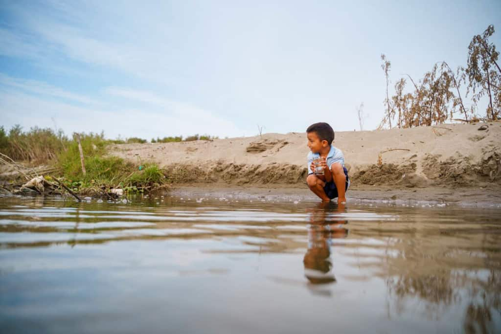 A child is kneeling down beside a river that runs in the Tamarindo community.