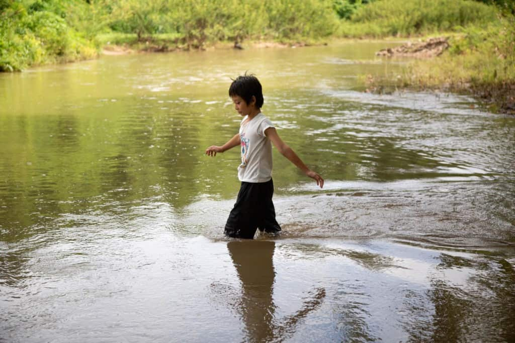 Girl wearing a white shirt and black shorts. She is walking into a stream near her village.