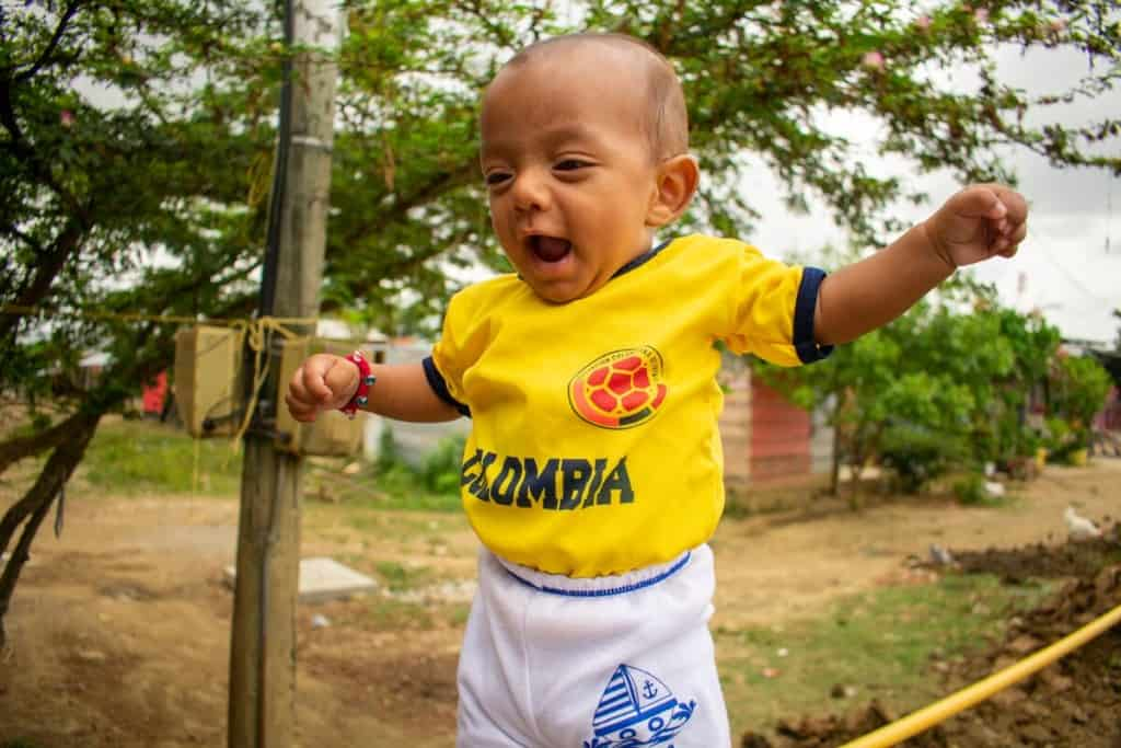 Baby Deinner is wearing a yellow Colombia football shirt and white pants with a sailboat on them. He is smiling and outdoors