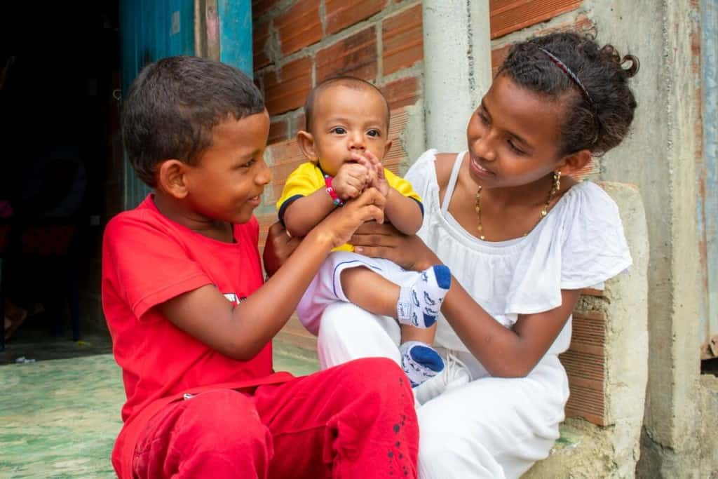 Baby Deinner and his older brother and sister are outside their home in Colombia