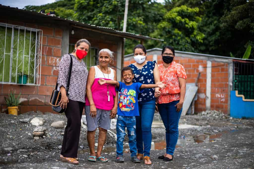 Jesus, wearing a dark blue shirt and jeans, is standing with his grandmother, Rosa, wearing a pink and white shirt and black and white striped shorts. Next to them is the project director and the tutors. They are standing outside Jesus' home. The Compassion staff are wearing face masks.