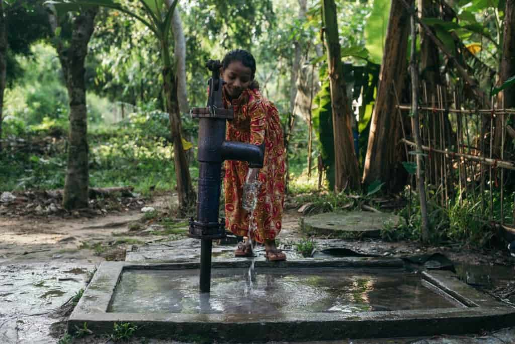Girl wearing a gold dress with a red paisley pattern. She is pumping water from the tube well at her home. There are trees behind her.