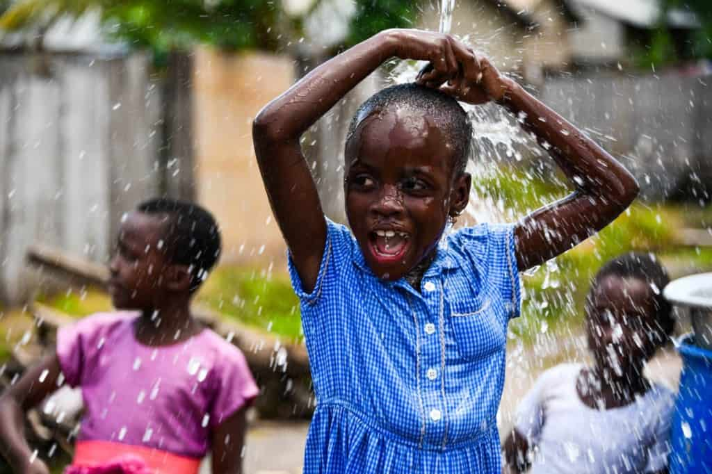 Girl wearing a blue and white checked dress. She is playing in water coming from the pipe to the borehole at the Compassion center. The water is running down over her head. Other children are in the background.