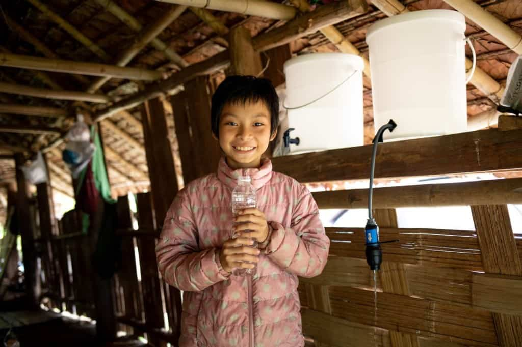 Girl wearing a pink jacket. She is inside her home and is holding a water bottle full of clean water.