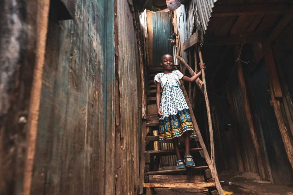 Girl wearing a white dress with a blue pattern. She is standing on a wooden stairway between two houses in the slums, where she lives with her family.