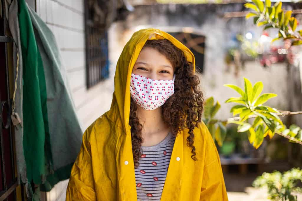 Girl standing in front of her home. She is wearing a black and gray striped shirt, yellow raincoat, and a face mask.
