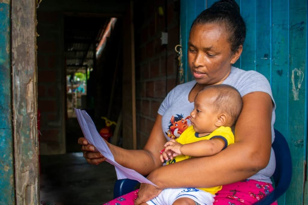 A grandmother is holding her newborn grandson and reading from a sheet of paper.