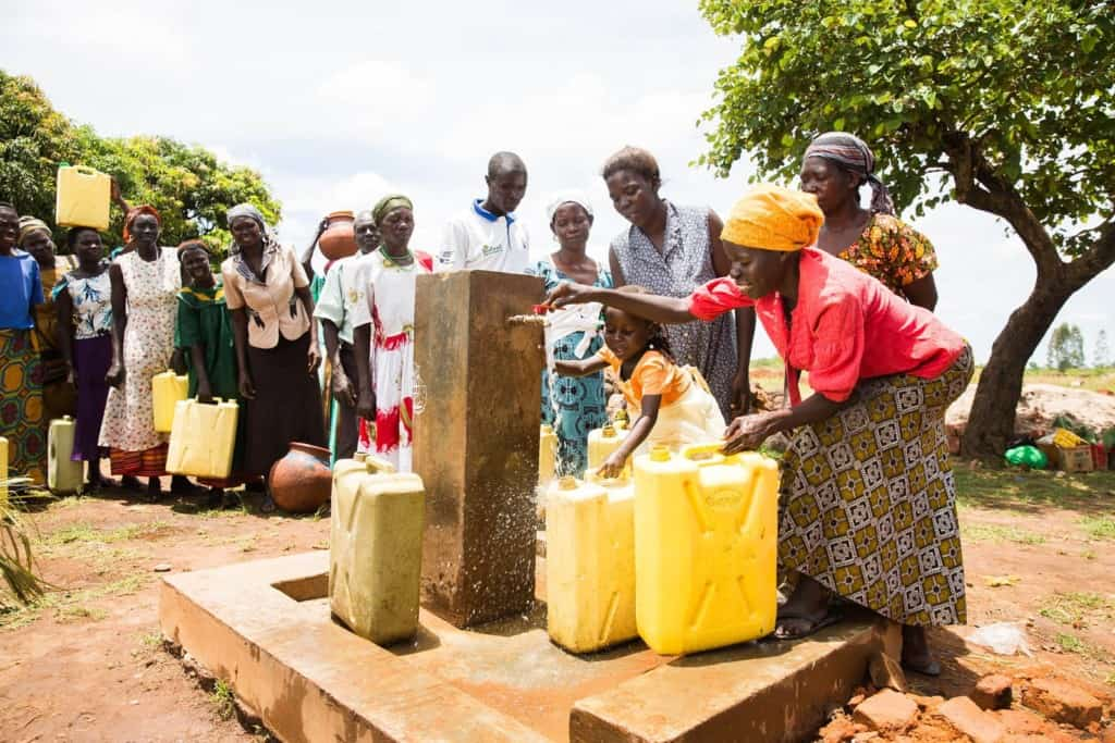 Woman wearing a yellow head scarf and a red shirt with a long pattern skirt smiles as she fetches clean water from an outdoor outside community faucet into her yellow plastic container Other women standing single file in line behind her to also fetch the clean running water. Girl wearing an orange and white dress helps her mother collect the life saving water.