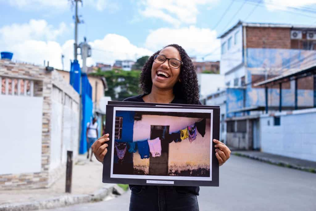 Rayane shows one of her favorite pictures. She is smiling at the camera as she holds up her picture.