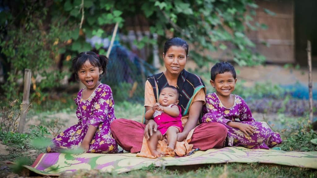 Mother and children  all sitting together on a blanket outside their home. Two of the chilren are wearing dark pink dresses with flowers on them.
