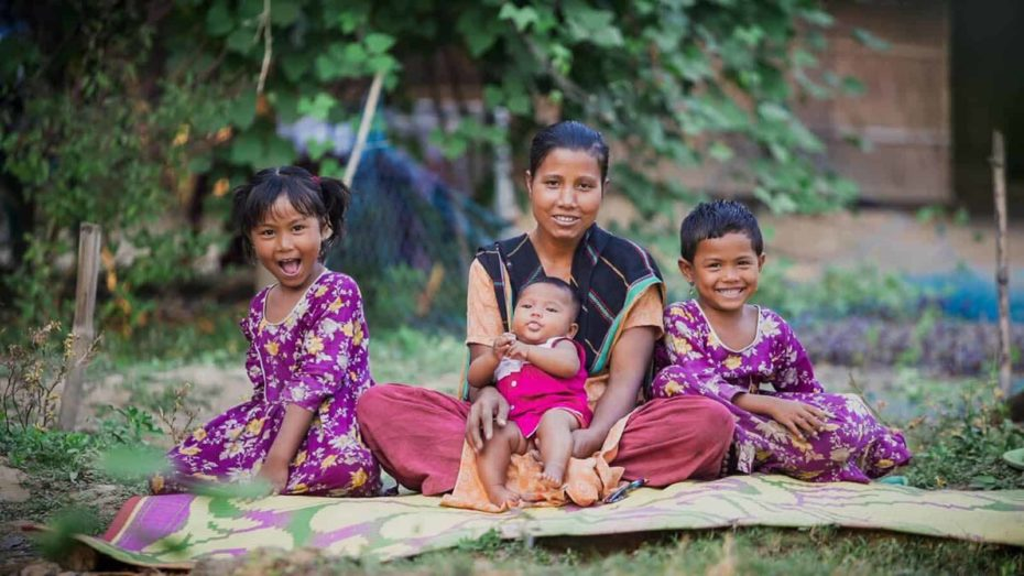 A woman and her three children sit on a mat outdoors. They are smiling. The two older children are wearing matching purple dresses