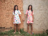 Sarah is wearing a pink patterned dress and Sophia is wearing a white patterned dress. They are standing in front of a brick and cement building and they are holding hands.