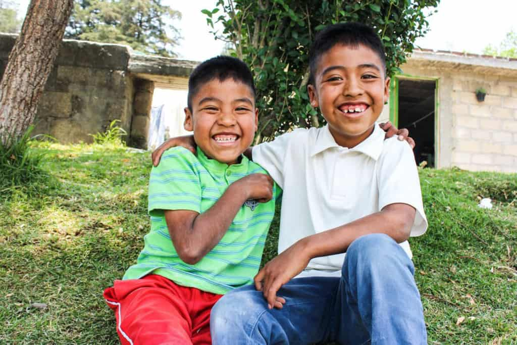 Jose, wearing a green shirt and red shorts, is sitting outside his home with his brother, Victor, wearing a white shirt and jeans. They have their arms around each other.