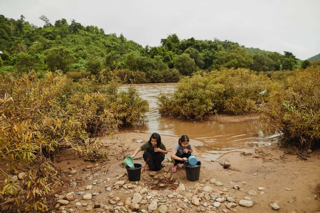 Two adolescent female teen girls, one in a green shirt and black skirt, the other in gray shirt and black pants, sit, squat on the rocky dirt ground holding green and blue pans, pouring water into black buckets. Behind them are a body of brown water, trees and shrubs.