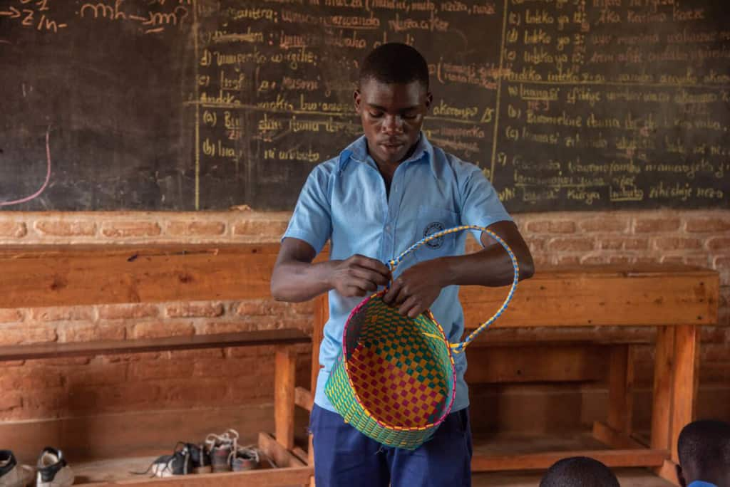 Sebastian is wearing dark blue pants and a blue shirt. He is teaching youth at the Compassion center how to weave bags in one of the classrooms. Behind him is a brick wall with a large black board on it.