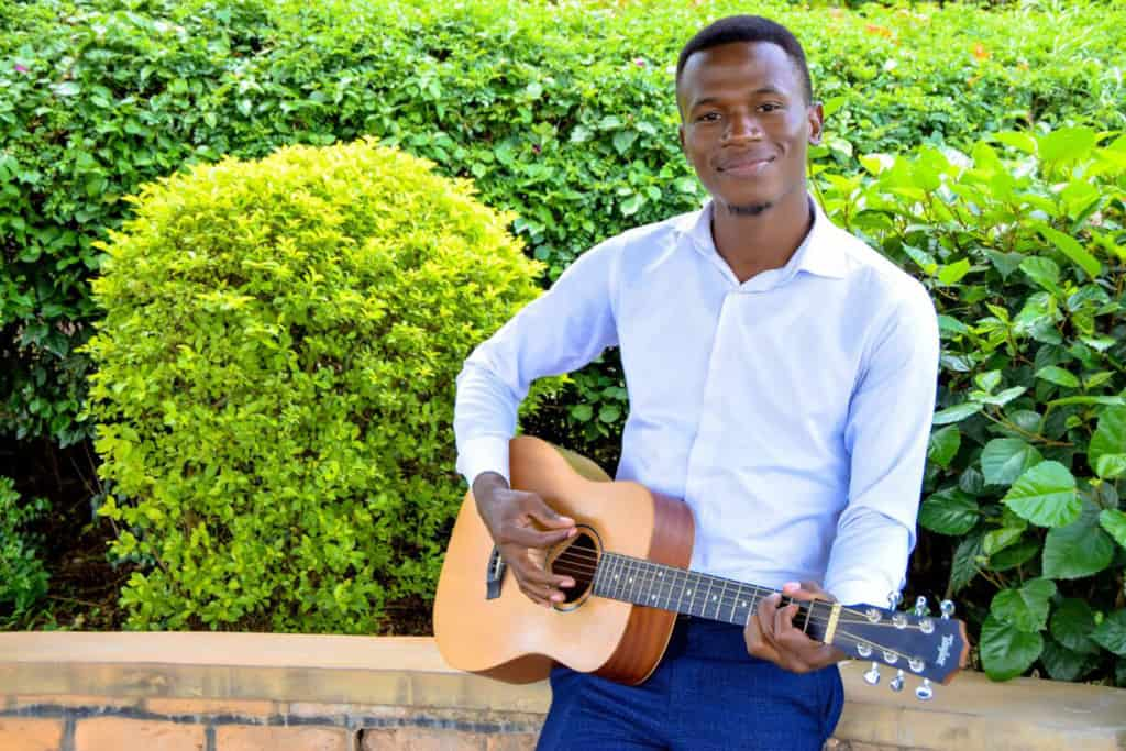 Faida is weairng a white shirt and navy blue pants. He is playing his guitar. Behind him are green bushes.