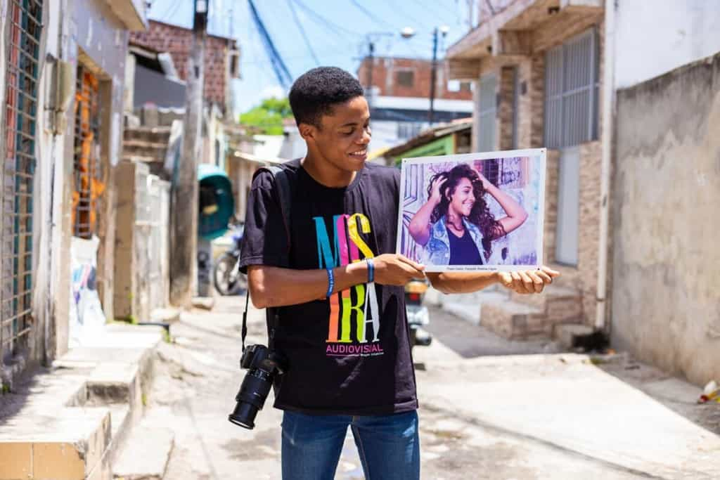Rhaldney shows one of his favorite pictures. He is wearing a black tee shirt with colored letters, and jeans. He is holding a photo and looking at it.