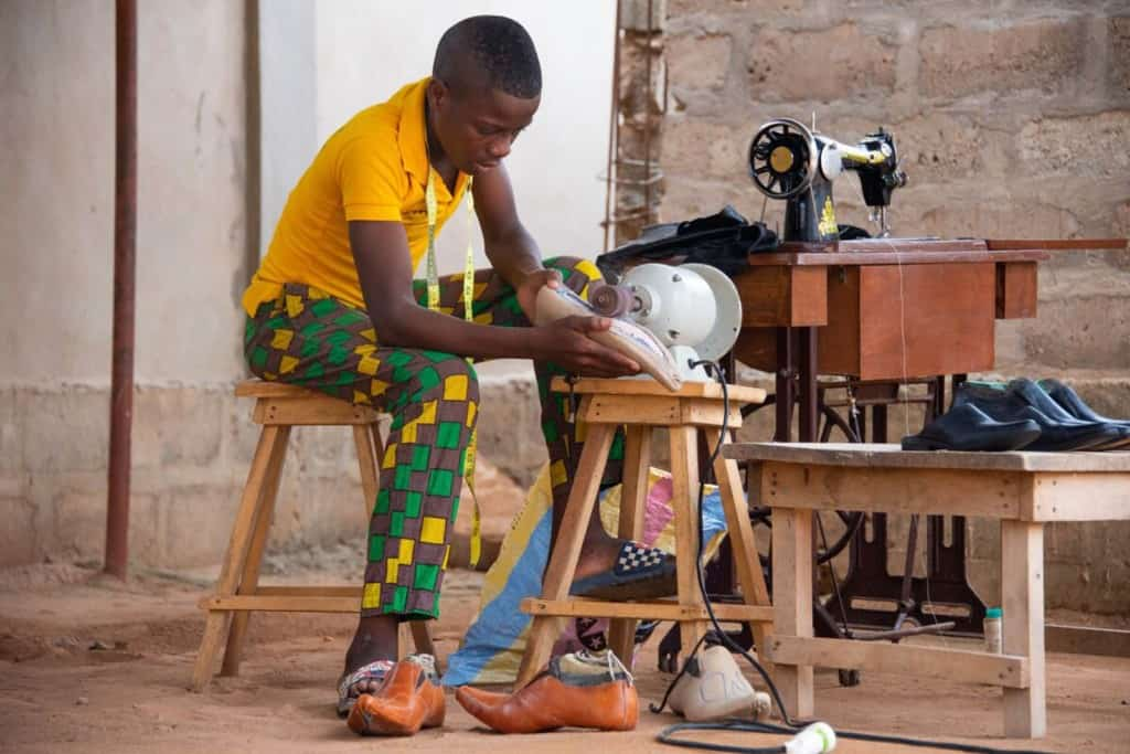 Theophile is wearing a yellow shirt. He is using a machine to polish a pair of shoes he is making.