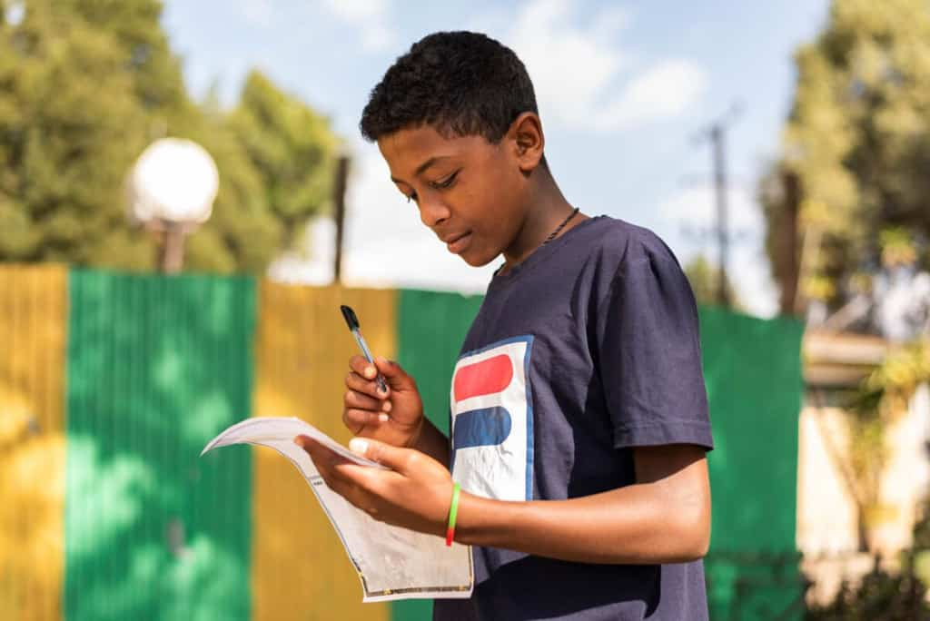 Young man wearing a blue shirt. He is standing outside and is writing a letter to his sponsor.
